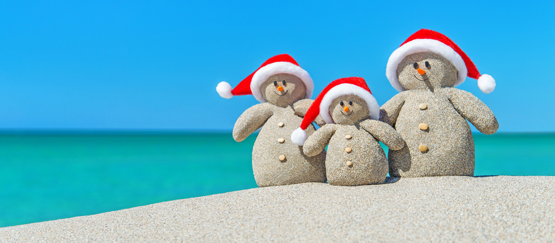 Family of Christmas Snowmen in santa hats at tropical beach.